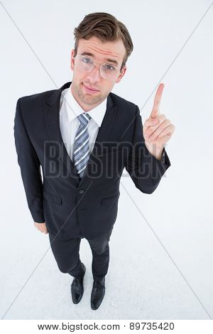 Geeky businessman with finger up on white background