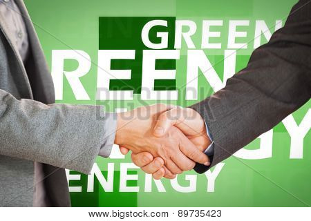 Two people having a handshake in an office against creative image of green energy concept