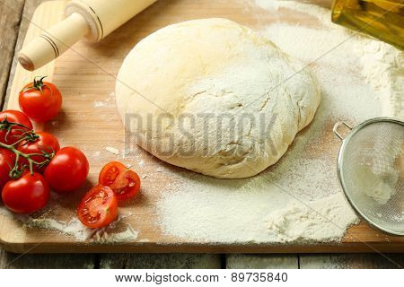 Dough on cutting board with cherry on table close up