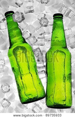 Glass bottles of beer on ice cubes background