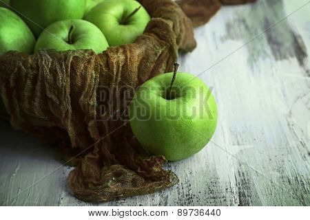 Green apples in bowl with fabric on wooden table, closeup