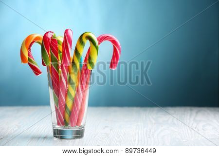 Colorful candy canes in glass on table on blue background