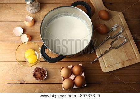Preparation cream with eggs in pan on wooden background