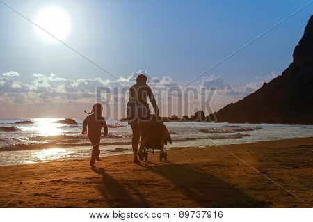 Mother With Her Daughter And Baby On A Sandy Beach