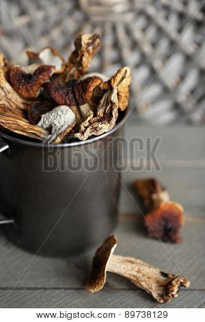 Dried mushrooms in metal cup on wooden background