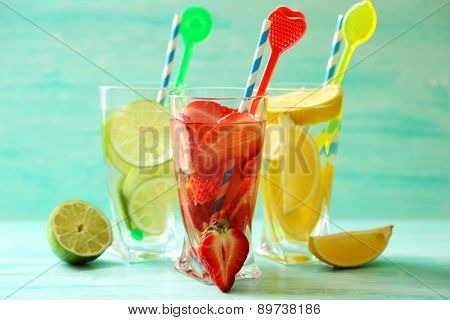 Cocktails with fresh strawberries and lemon lime on wooden background
