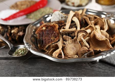 Dried mushrooms with spices on wooden background