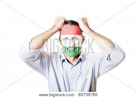 Mature man with Hungary flag painted on face.