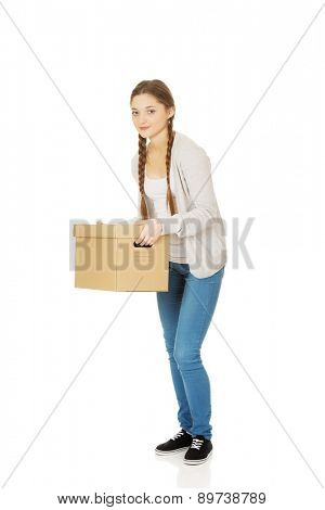 Tired teenage woman holding heavy carton box.