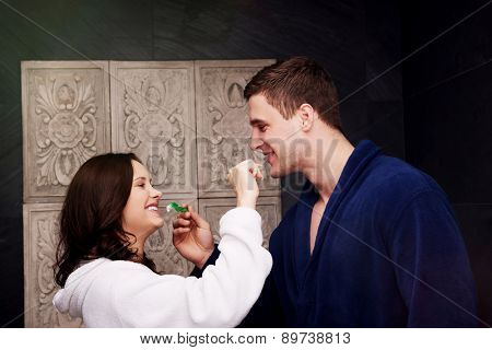 Beautiful couple in the bathroom brushing teeth.