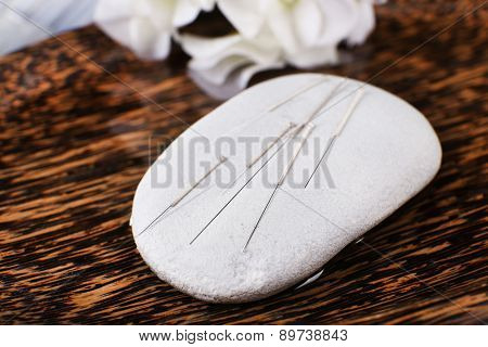Acupuncture needles on wooden plate with spa stone, closeup