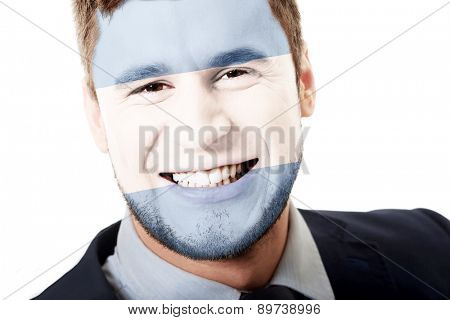 Happy man with Argentina flag painted on face.