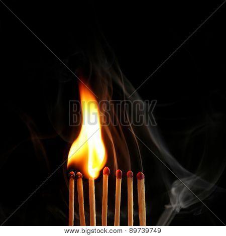 Burning matches in smoke on black background