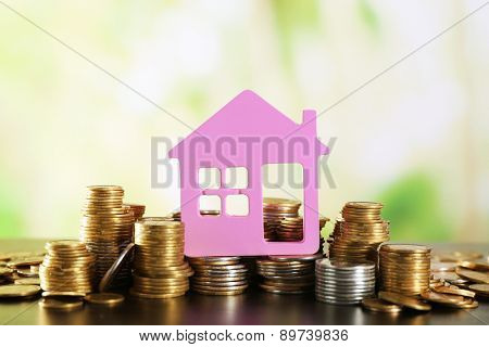 Model of house with coins on wooden table on blurred background