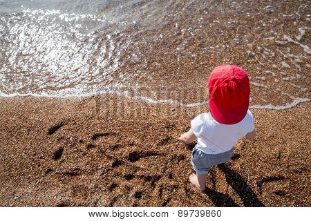 Cute boy playing and having fun on the beach. Little boy playing in the pebbles on the beach