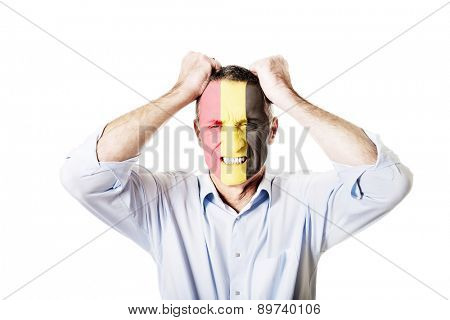 Angry mature man with Belgium flag painted on face.