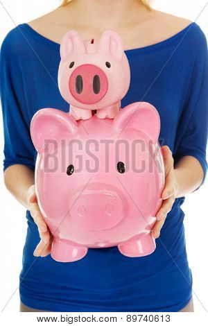 Casual woman holding two piggybanks.