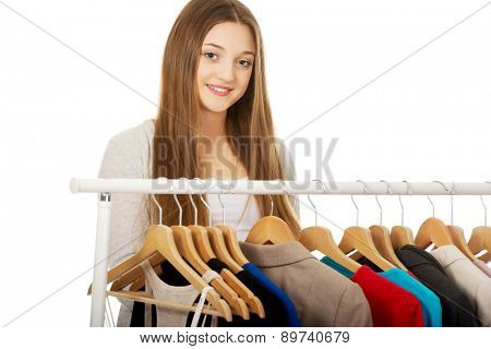 Happy teen woman thinking what to put on.