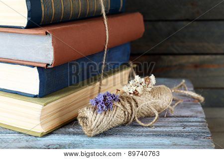 Stack of books with dry flowers on table close up