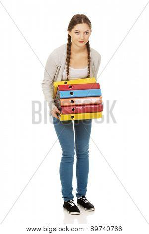 Happy teen woman holding heavy binders.