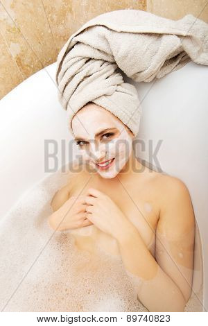 Young spa woman relaxing in bathtub with cream moisturizer.