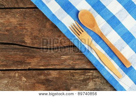 Checkered napkin with spoon and fork on wooden table background