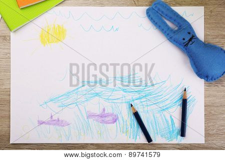 Kids drawing on white sheet of paper with crayons on wooden table, closeup