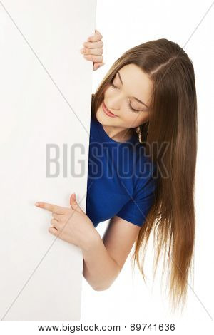 Young teenage woman pointing on blank board.