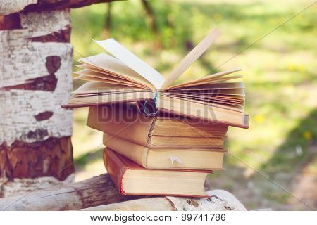 Stack of books on bench, outdoors