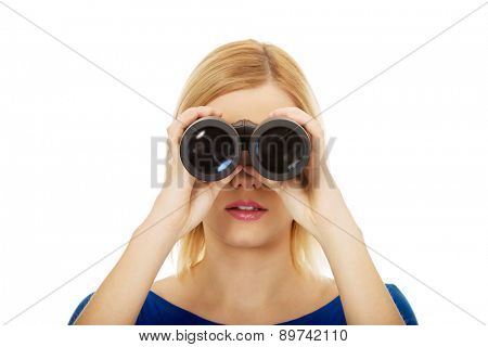 Young woman looking through binoculars.