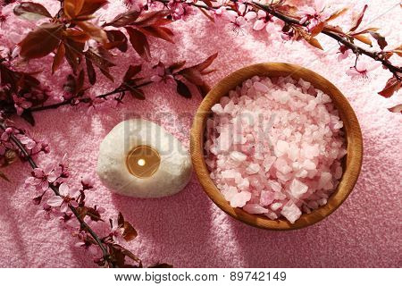 Sea salt in bowl with candles and spring flowers on towel background