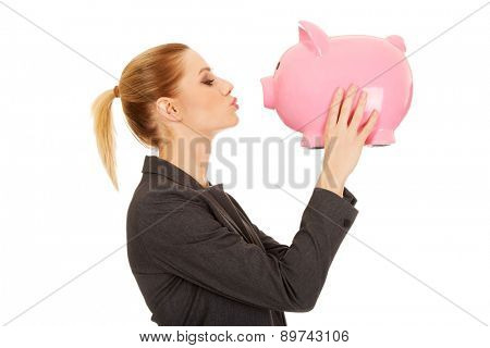 Beautiful business woman kissing a piggybank.
