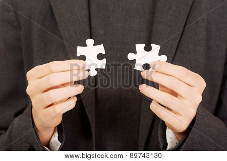Businesswoman connecting two puzzle pieces.