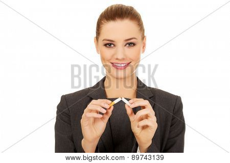 Smiling business woman breaking cigarette.
