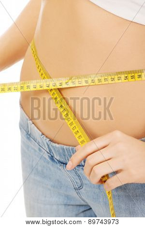 Slim woman measuring her waist.