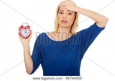 Unhappy woman holding an alarm clock.