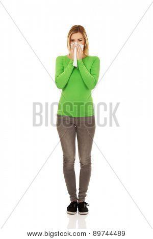 Unhealthy woman sneezing to tissue.