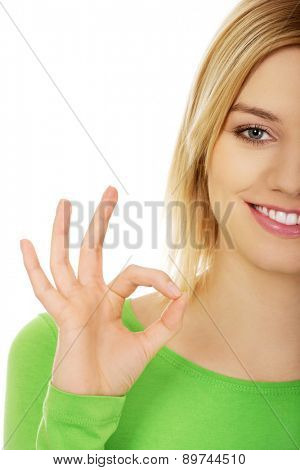 Happy woman gesturing perfect sign with hand.