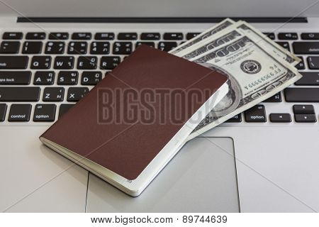 Passport with us dollars on laptop
