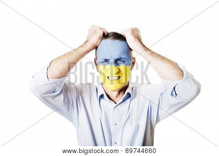Mature man with Ukraine flag painted on face.