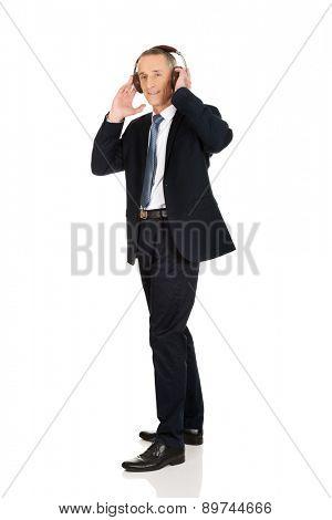 Mature businessman with big headphones.