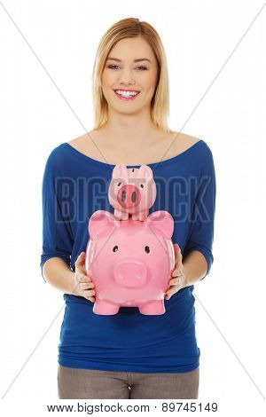 Happy casual woman with piggybanks.