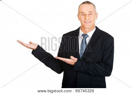 Portrait of businessman with welcome gesture.