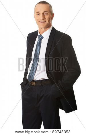 Confident mature businessman with hands in pockets.