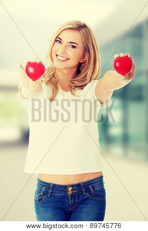 Smiling woman with red heart in her hand