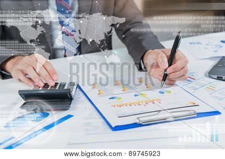 Businessman Analyzing Report On Chart With Laptop And Calculator