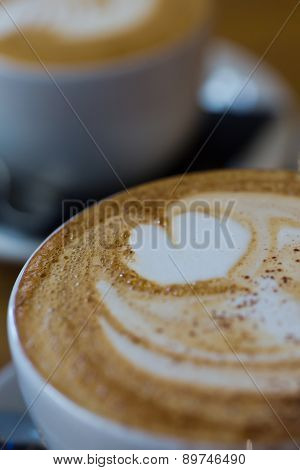 A Close-up Photo Of A Cappucino With A Flat White In The Background
