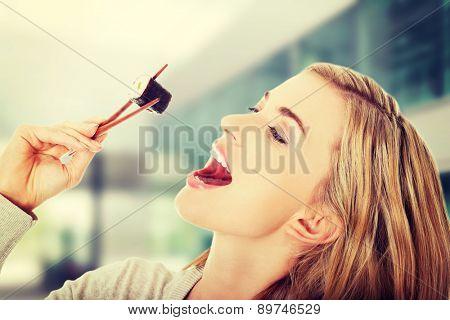 Happy woman eating tasty sushi
