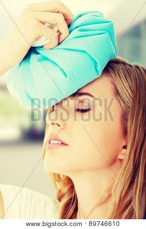 Beautiful woman with ice bag having headache.
