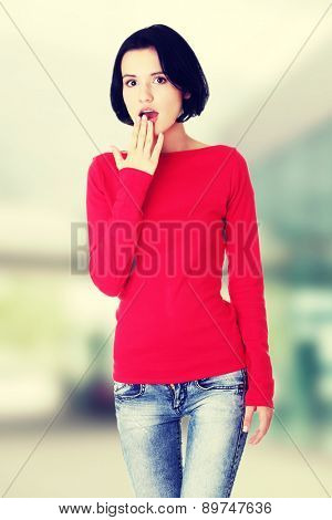 Young woman covering her mouth.